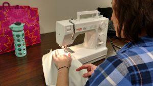 Volunteer sews a garment protector.