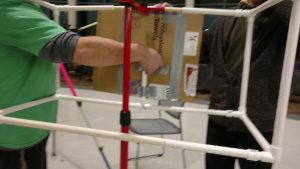 Volunteers construct an art easel from PVC pipe