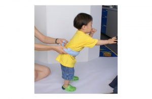 Demonstration of walking support for child using dishtowel.